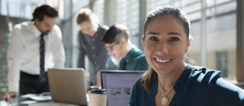 Equipo de trabajo frente a un computador. En primer plano, una mujer sonríe a la cámara.