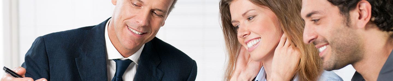 Imagen de pareja recibiendo asesoría de un ejecutivo de seguros en sucursal.