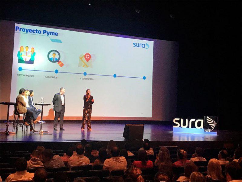Imagen de colaboradores de SURA exponiendo en una conferencia.