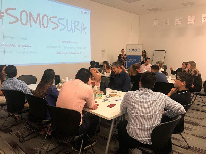 Imagen de un grupo de colaboradores de SURA sentados en una mesa participando en un taller.