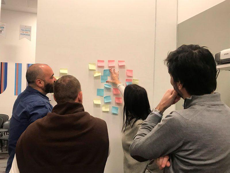 Imagen de tres participantes de SURA colocando post its en una pizarra durante un taller para colaboradores.